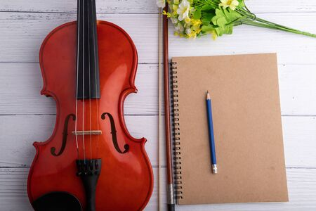 Close-up shot violin orchestra instrumental and notebook over white wooden background select focus shallow depth of field Stok Fotoğraf