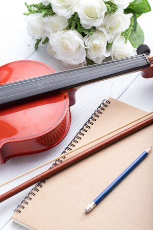 Close-up shot violin orchestra instrumental and notebook over white wooden background select focus shallow depth of field Stock Photo