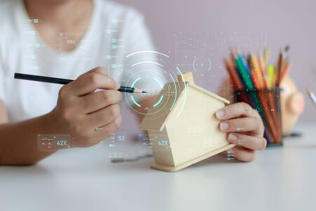 Happy Asian woman using pencil to draw with wooden house piggy bank and Cyber technology HUD GUI user interface metaphor design and decoration the house select focus shallow depth of field