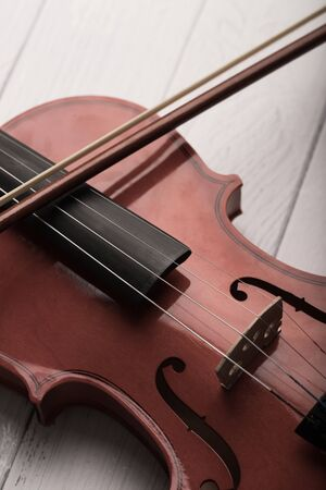 Close-up shot violin orchestra instrumental with vintage tone processed over white wooden background select focus shallow depth of field