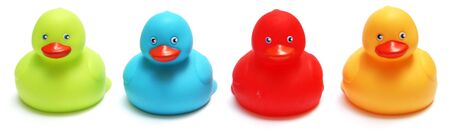 four bath rubber duck toys in green, blue, red and yellow photo
