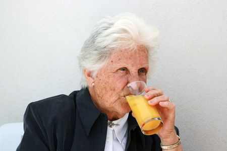 octogenarian: smart old lady drinking a cold glass of orange juice Stock Photo