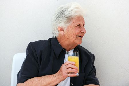 octogenarian: smart happy old lady with a glass of fresh orange juice