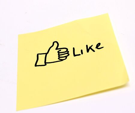 post it note: Like with the thumbs up symbol written on a sticky note Stock Photo