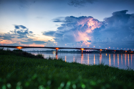 lao: lightning over the bridge of thai and lao friendship bridge; forground is blur soft focus.