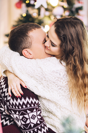 Happy couple dressed in the sweaters is kissing and hugging near the christmas tree, cozy atmosphere and love, home and family, white caucasian couple