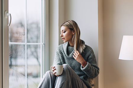 Beautiful white stylish woman in cozy scandinavian interrior sits at home near the big window, portrait of the beautiful girl, fashion portraits, woman with style