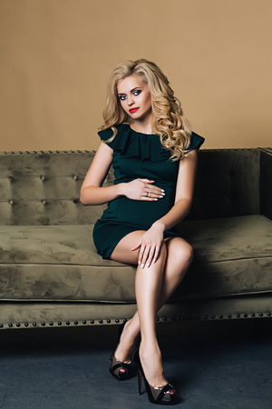 99a7ea0b3d24f Beautiful and stylish pregnant caucasian woman with blond hair holds her  belly, stylish pregnancy photo
