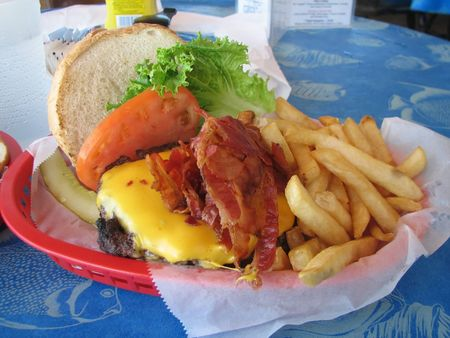 broil: Shot of a hamburger with cheese, bacon, tomato, lettuce, and french fries.