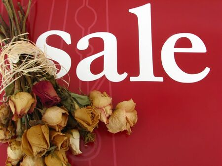 dried bouquet over a sale sign.