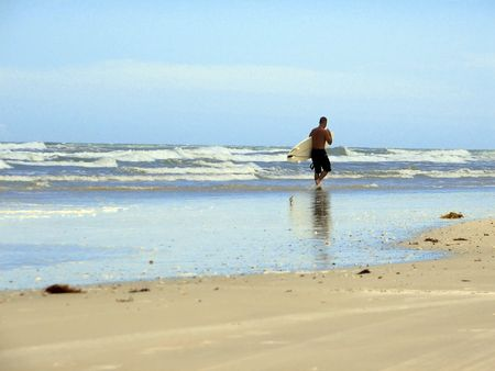 Shot of a surfer walking on the shore at New Smyrna Beach in Florida. photo