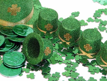 patron saint of ireland: Shot of a few green top hats with a shamrock confetti and metallic green coins.  Over white.
