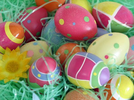 Closeup of several Easter eggs over green artifial grass and a flower.