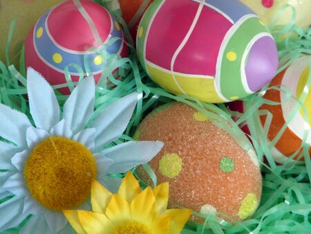 Closeup of several Easter eggs over green artifial grass and a couple flowers. photo