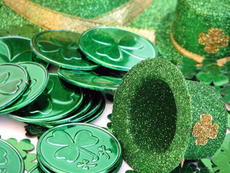 patron saint of ireland: Shot of several green coins with a shamrock on it.  A green hat with a shamrock is laying next to the coins.  Over white.