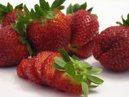 edibles: Shot di pochi fragole su bianco ..., uno di loro � tranciato. Archivio Fotografico
