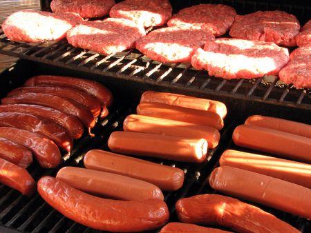 edibles: Shot di alcuni hot dog, hamburger, salsicce e caldo sulla griglia.