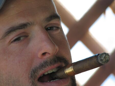 Shot of a mature white man with a cigar on his mouth, looking at the camera.  The man has mustache and goatee.