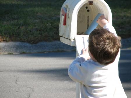 Een kleine drie jaar oud jongetje om de post uit de brievenbus. Stockfoto
