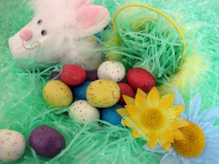 Shot of a traditional decorated Easter basket with some flowers and several eggs, very colorful. photo