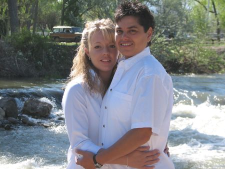 fem: Shot of two woman, a lesbian couple, smiling for the camera, in River Bottle Park, Montrose Colorado.