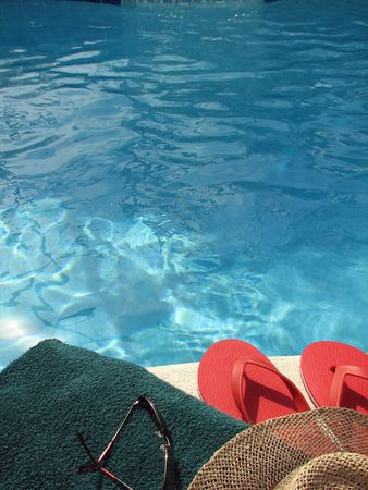 Shot of a towel, sunglasses, hat and sandals by the pool. photo
