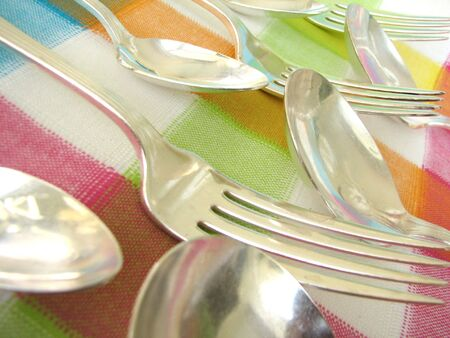 Macro shot of several forks and spoons lined up over a colorful tablecloth.