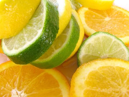 comestible: Closeup of a limon, lime, and an orange cut it in slices over ice.