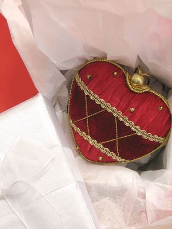 Closeup of a decorated red Heart in an open gift box, the lid of the box is on the side.
