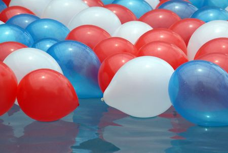 Shot of several balloons, red, blue, and white floating in a pool.  The balloons were used as decoration on 4th of July.