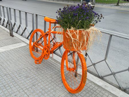 bike painted orange with flowers in the basket parked on the sidewalk photo