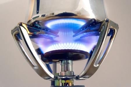 Camping gaz burner heats a metal pot photo