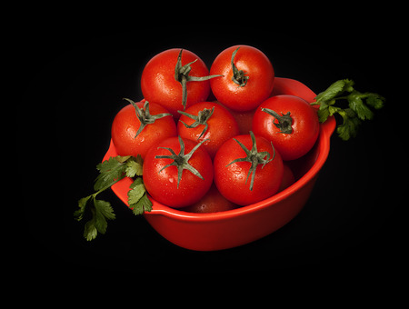 Cherry tomatoes and coriander isolated on black background photo