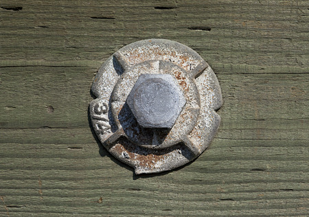 A very solid metallic hex bolt with washer fixing the handrail to the wooden bridge post  Stock Photo