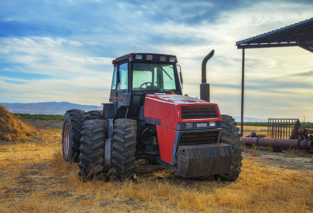 wheeled tractor: Abandoned Tractor on the Field, sunset. Tractor is specifically designed to deliver a high tractive effort at slow speeds, for the purposes of hauling a trailer or machinery used in agriculture or construction. Stock Photo