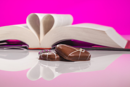Book of love isolated on pink background. Love inspired stories show that faith, forgiveness and hope have the power to lift spirits and change lives, always.