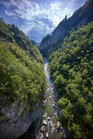 brige: mountains with small river deep below from a brige