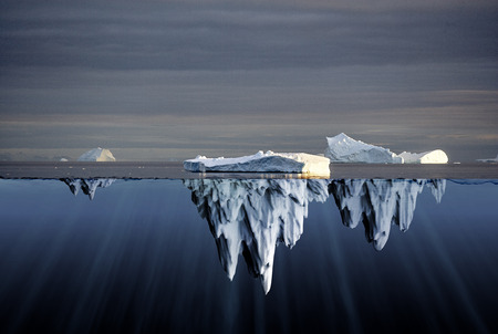 Above and below water view of icebergs in the Antarctica showing the volume of ice below the surface of the ocean and the consequent danger to shipping Stock Photo