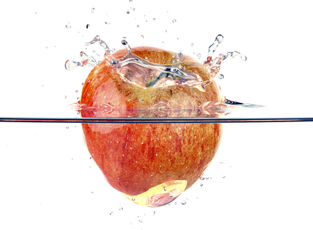 fluidity: red apple faling and splashing into clear water Stock Photo