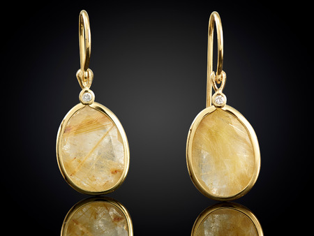 Golden earrings with gemstone isolated on black background. Stock Photo