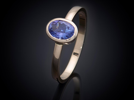 diamond shaped: silver ring with gemstone isolated on black background. Stock Photo