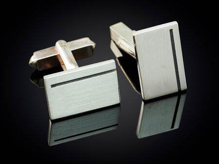 cuff link: beautiful silver cufflinks on black background.