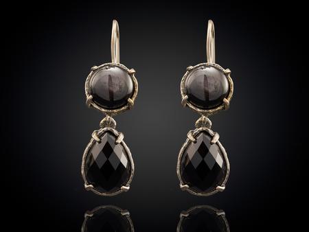 diamond shaped: Golden earrings with gemstone isolated on black background. Stock Photo