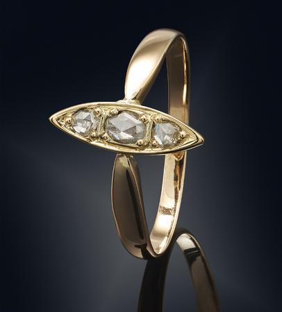 diamond shaped: Golden ring with gemstone isolated on black background.