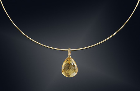 Golden necklace with gemstone isolated on black background.