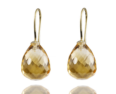 Golden earrings with gemstone isolated on white background. Stock Photo