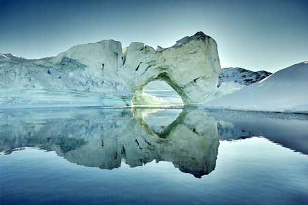 iceberg floating in greenland fjord.