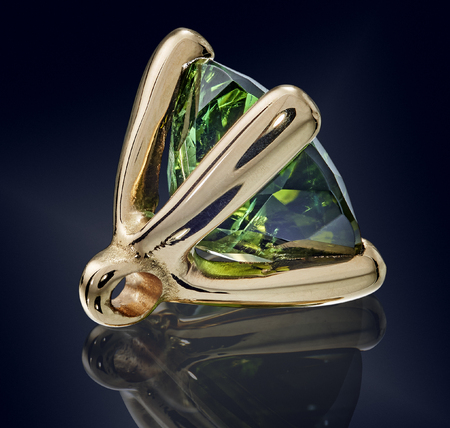 emerald gem stone in golden setting isolated.