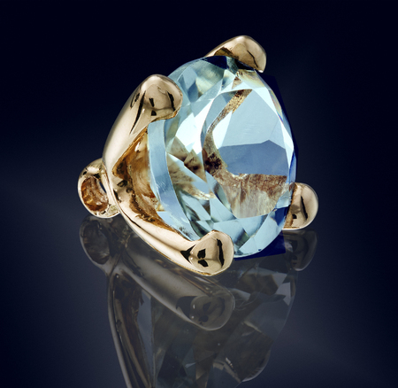 topaz swiss gem stone in golden setting isolated.