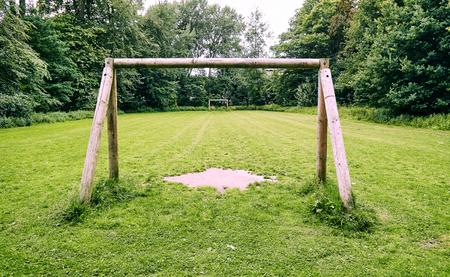 wooden soccer goal on grass field.